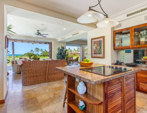 Tiled kitchen with induction stove on large island with koa cabinetry facing living area and open sliding doors to golf course and ocean views beyond.