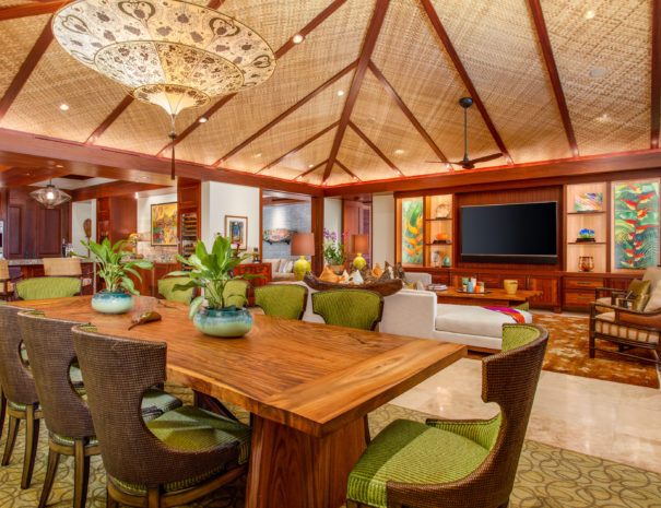 Large wooden dining table under beautiful light fixture and custom woven high ceilings with living room area beyond