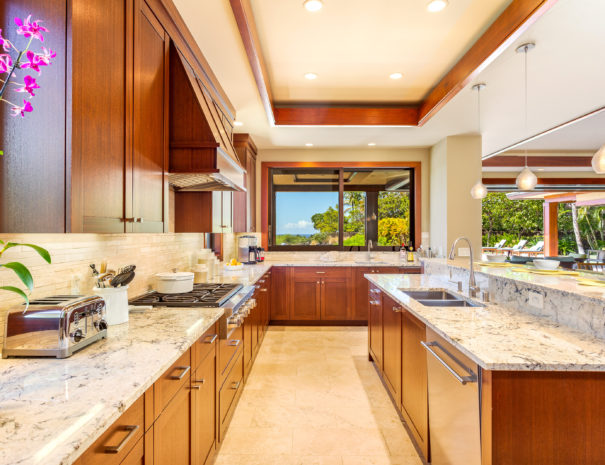 Marble countertops in kitchen area with island and stove facing window