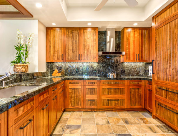 Tiled kitchen with dark marble countertops, and beautiful wooden cabinets.
