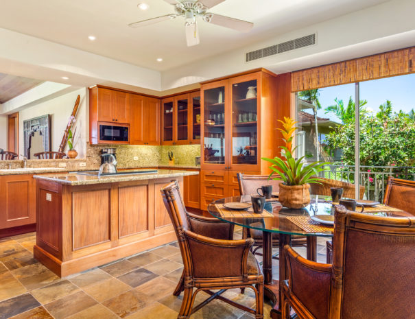 Tiled kitchen with chairs tucked around a glass dining area and island and cupboards in the background.