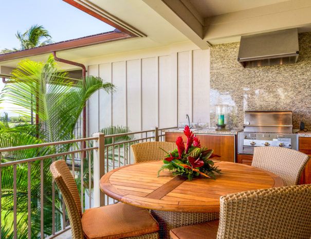 Tropical flower arrangement on circular outdoor table surrounded by four chairs and outdoor grill on lanai with palm trees peeking over balcony
