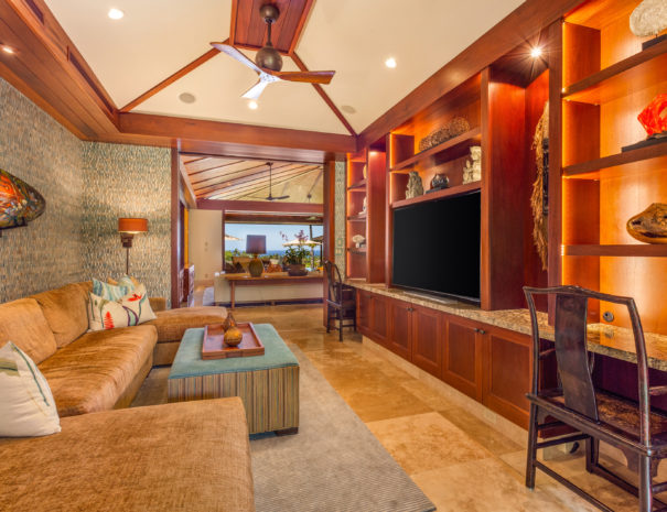 Separate entertainment den with beautiful wall paper and artfully decorated entertainment center with comfortable couch and large curved television.