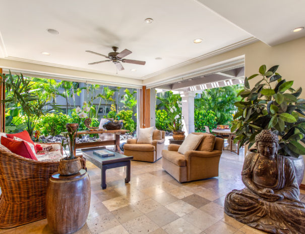 Marble living area with indoor plants, statues, comfortable seating, and open sliding doors to tropical foliage beyond.