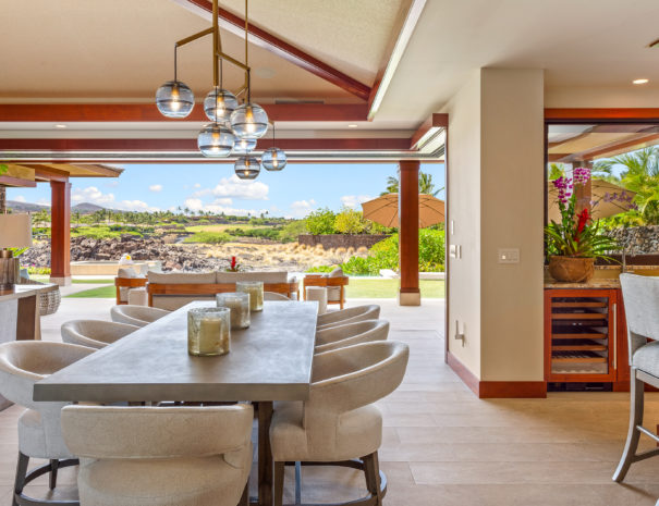 Large dining table with white chairs overlooking Hualalai Golf Course