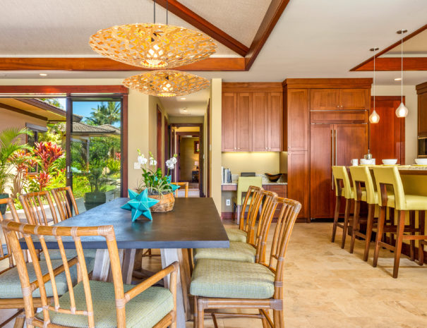 Dining area with table and chairs underneath light fixture facing kitchen and entry