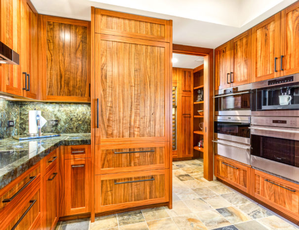 Well-equipped kitchen with beautiful wood cabinetry, marble counters, and quality appliances with pantry door open.