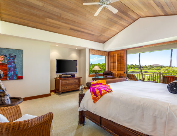 High ceiling above carpeted master bedroom with comfortable seating, desk, television, large bed with bright sarong on the bed and doors open showing comfortable seating.