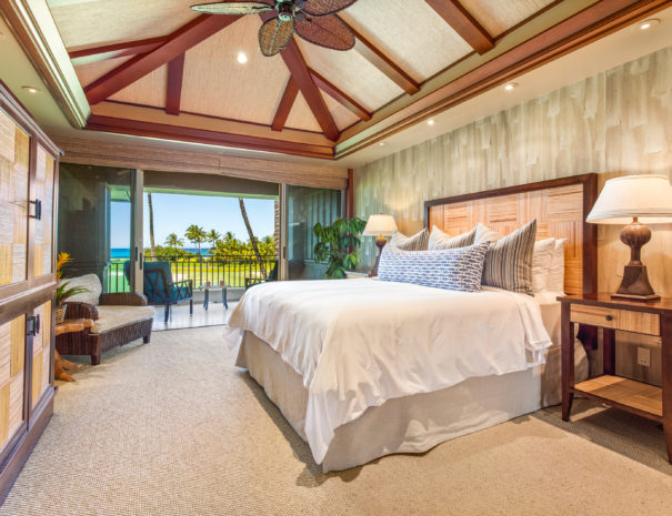 Carpeted master bedroom with textured walls and matching furniture and high ceilings leading up to a private lanai on the second floor with views of a golf course and ocean beyond.