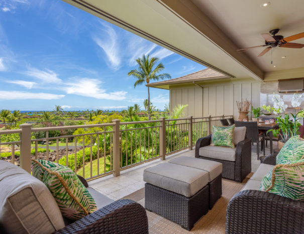 Large outdoor lanai showing comfortable lounge seating and dining table in front of outdoor grill and expansive views of Hualalai Resort