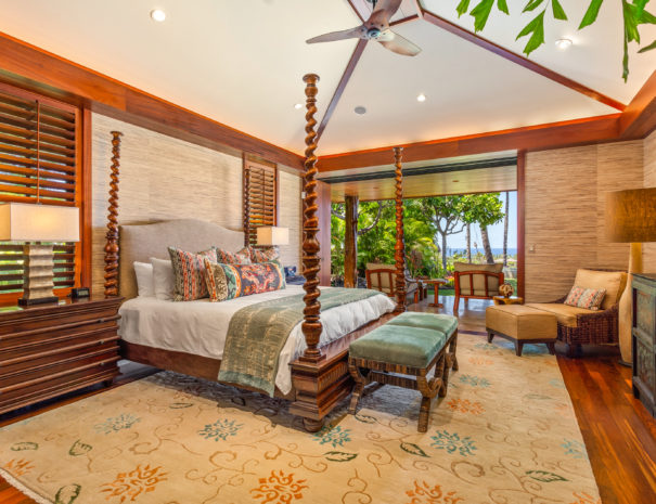 Large master bedroom with luxurious furniture and bed with view beyond to lanai