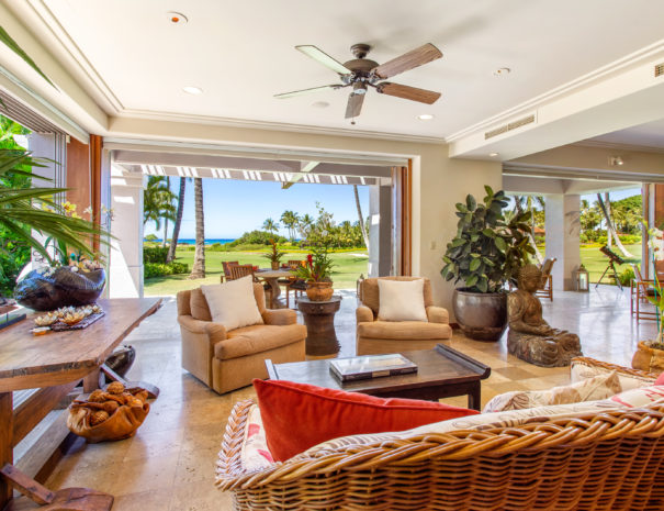Comfortable seating with large house plants and art facing out toward open door and lanai.