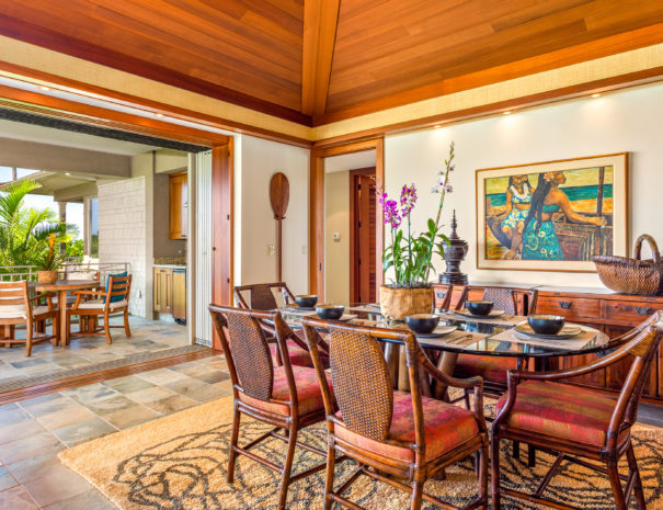 Tiled dining area with glass table set for dining and multicolored chairs and artwork on the walls with open sliding door showing outdoor furniture on lanai in the background.