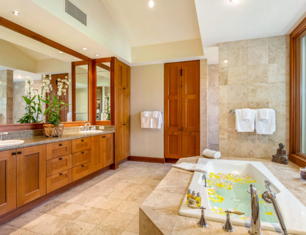 Large, tiled bathroom with bathtub full of water and flower petals across from large double vanity.