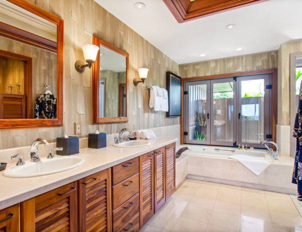 Large master bedroom with textured walls, a large double vanity with wooden cabinets across from a robe and showing a full bathtub beyond.