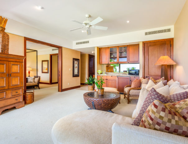 Carpeted downstairs retreat with kitchenette area and comfortable furniture facing open doorway of master bedroom beyond