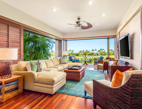 Large couch in a welcoming living room facing television with comfortable outdoor furniture past large sliding doors in Hualalai Resort villa