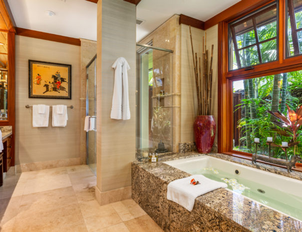 Luxurious bathtub filled with water and shower in the background with large window showing lush private garden outside