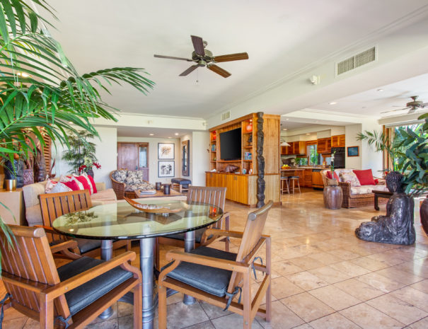 Tiled table with large palm trees facing toward living area, den, and kitchen in the background.