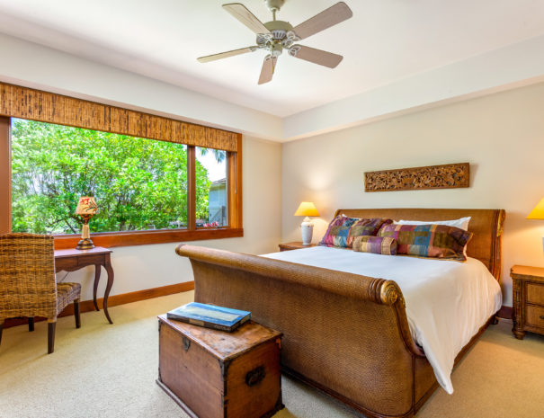 Carpeted bedroom with large bed with multicolored pillows, a wooden chest, and a desk facing out the window.