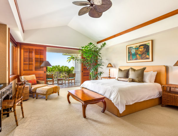 Carpeted master bedroom showing art on the walls, comfortable chair, a desk, large indoor plant, and lit lamps.