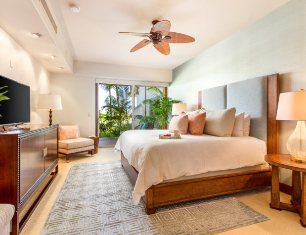 Welcoming master bedroom with luxurious decorations and serving tray on the edge of a bed facing television and lit up lamps