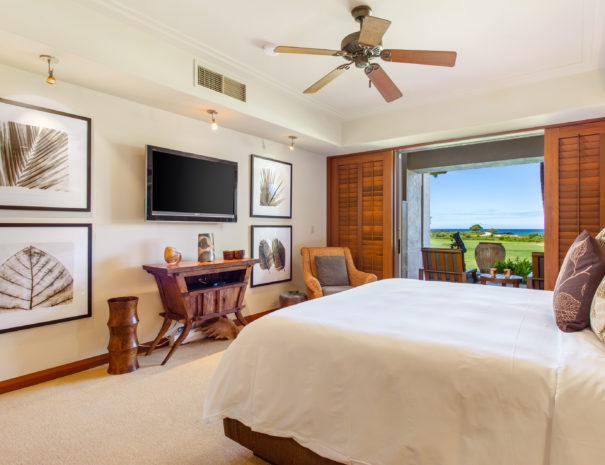 Carpeted master bed facing television and art on the walls, a chair with open sliding door showing two chairs facing ocean and golf course views.