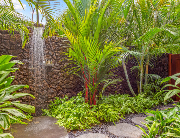Water spraying from an outdoor shower with rough lava rock and tropical foliage