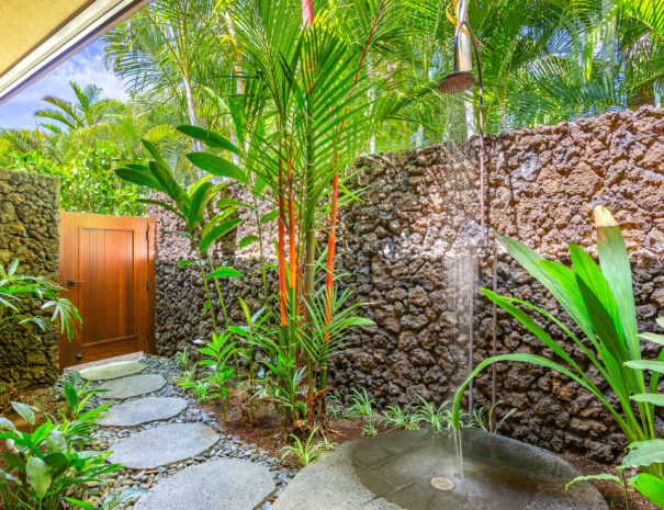 Water running from outdoor shower with lava rock and tropical backdrop showing path leading to gate