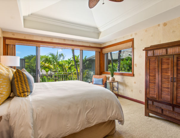 Second floor carpeted bedroom with natural fiber wall paper and a large bed across from an armoire and a chair with side table next to window showing tropical foliage.
