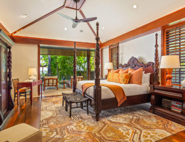 Luxurious master bedroom with large four post bed and wooden shutters in front of windows
