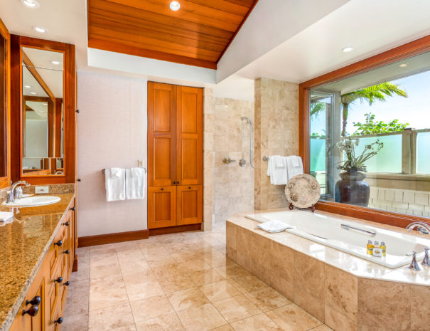 Tiled master bedroom with bath tub beneath large window across from a double vanity and large walk in shower in the background.