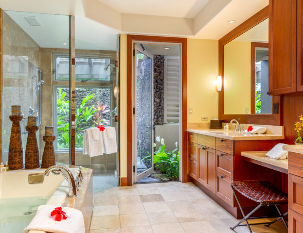 Inviting tiled master bathroom with tub filled with water showing large stand up shower and door open to outdoor shower area beyond