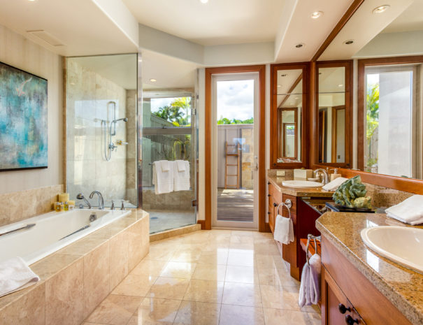 Luxurious tiled bathroom with large bath tub and glass shower showing outdoor shower area and double vanity
