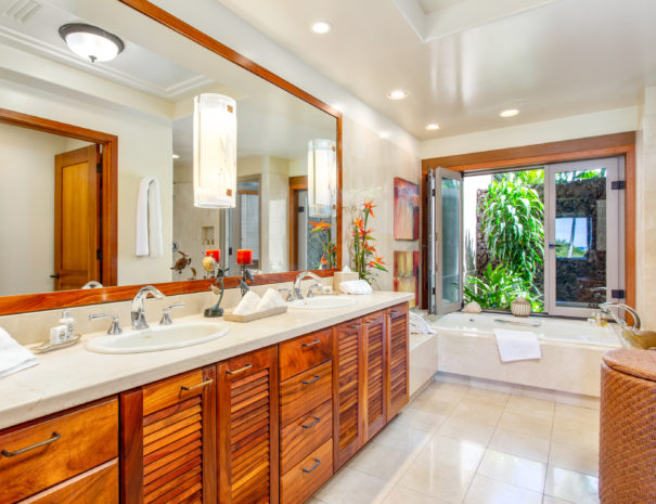 Large tiled bathroom with double marble top vanity with koa cabinetry leading to a large bath tub underneath an open window