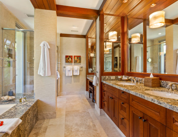 Luxuriously tiled bathroom with marble tub and double vanity with another marble vanity and shower in the back