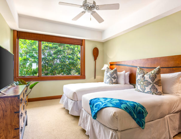 Carpeted guest room with two double beds facing a dresser with television on top and large window shows green foliage outside.